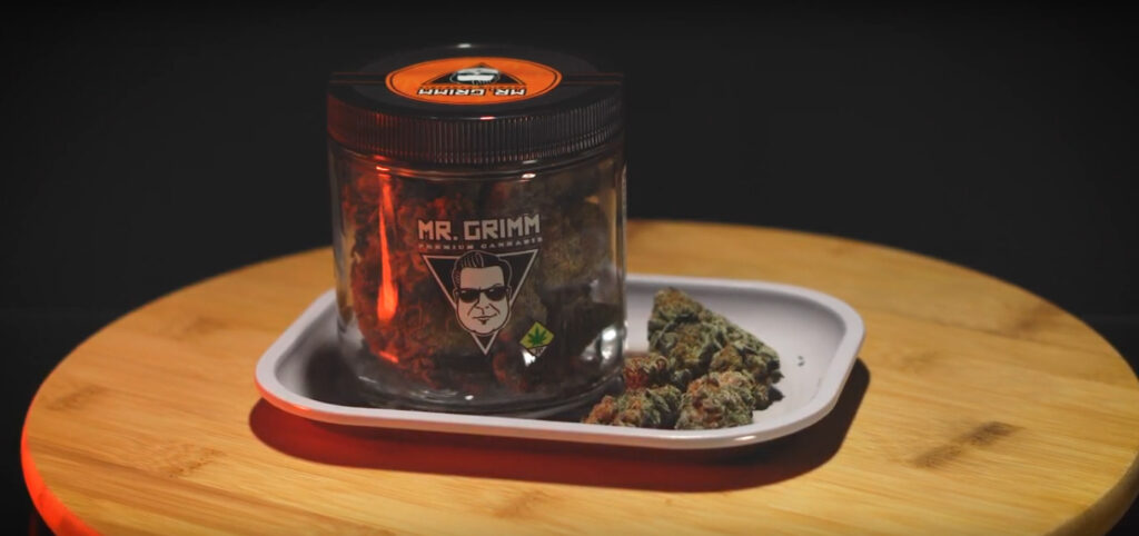 An ounce of Peanut Butter Breath by Mr. Grimm bathed in orange light on a product lazy susan, with a rolling tray and some loose nugs.